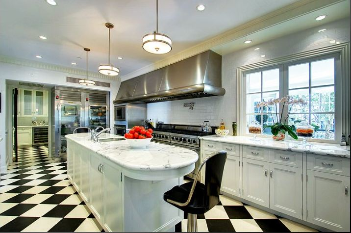 Paul williams estate 28 million dollar home kitchen marble countertops gourmet stainless appliances black white checkered floor laid on diagonal island 2